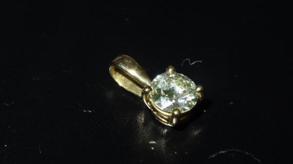 Pendentif en or jaune 18K (750°/00) orné d'un diamant rond demi-taille d'environ[...]
