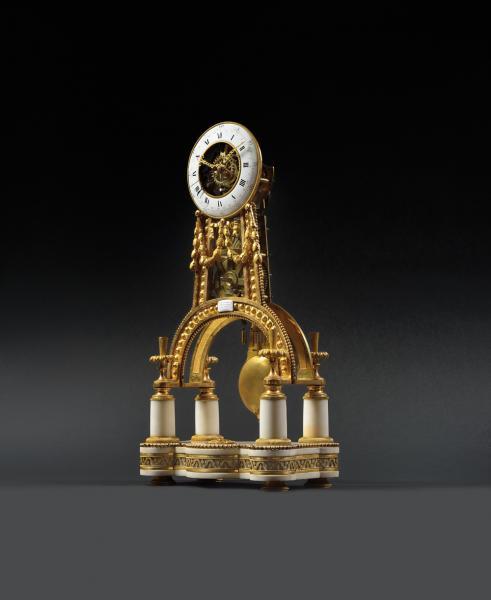 PENDULE SQUELETTE en bronze doré et ciselé, le piétement en arc repose sur une[...]